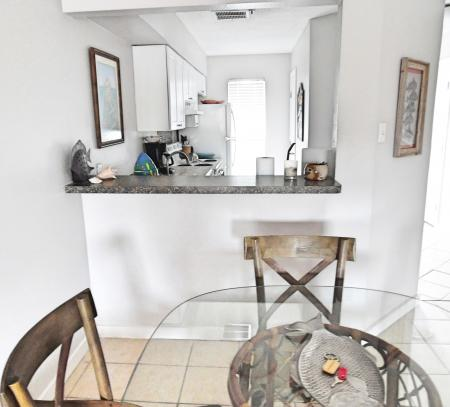 Click to enlarge image Open dining to kitchen - BeeGee's Redfish Quarters - Large 2 bedroom, 2.5 bath with tile and laminate floors, private laundry, Dog Friendly. Walk to the beach. Covered Patio.