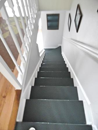 Click to enlarge image Stairs from 2nd floor looking down - BeeGee's Redfish Quarters - Large 2 bedroom, 2.5 bath with tile and laminate floors, private laundry, Dog Friendly. Walk to the beach. Covered Patio.